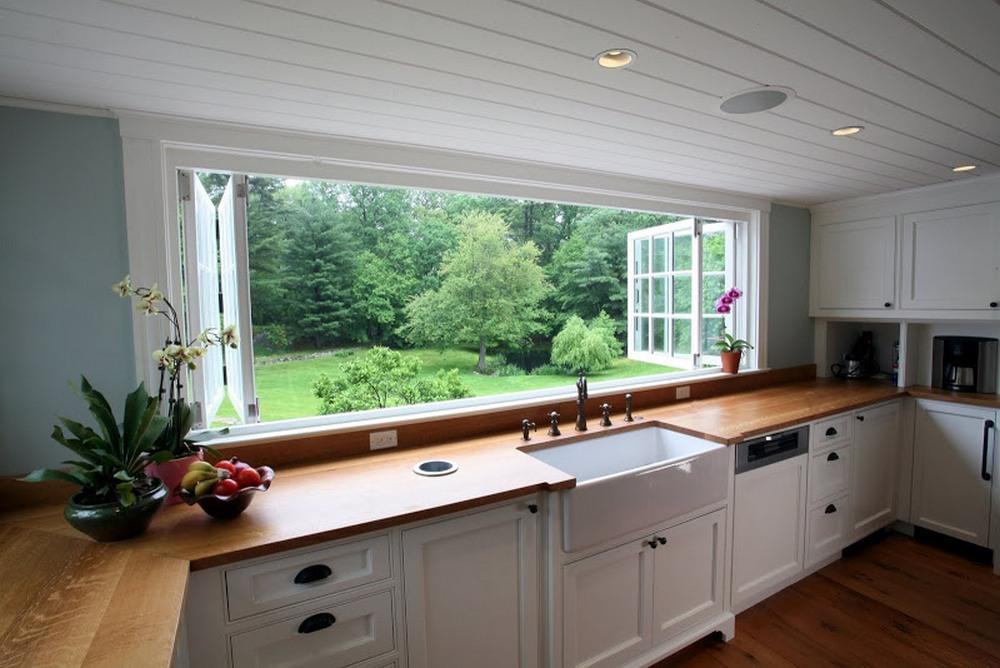 Кухонная мойка у окна квартиры или дома с видом на улицу